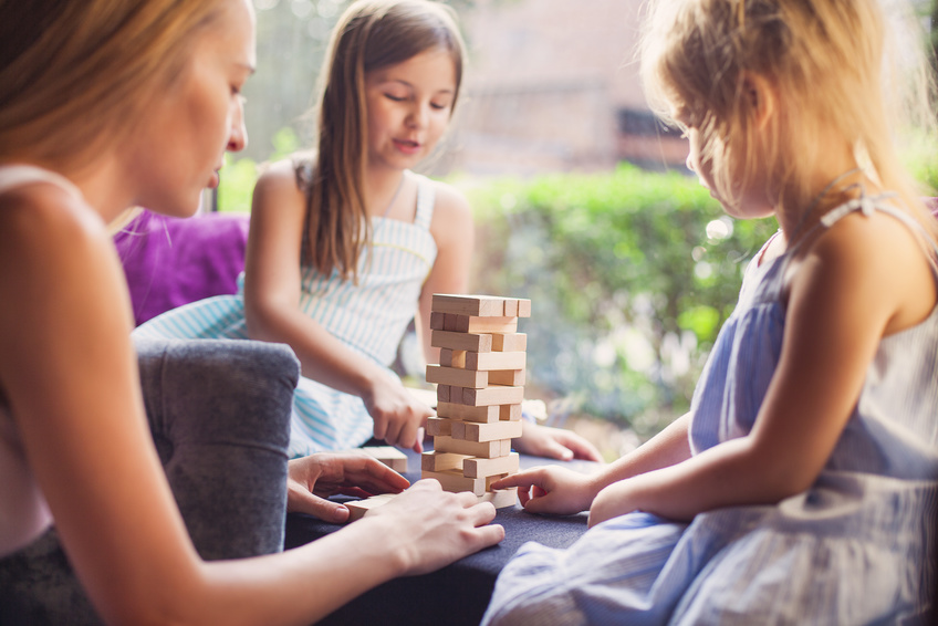 Happy mother with two children playing the wooden blocks tower at home